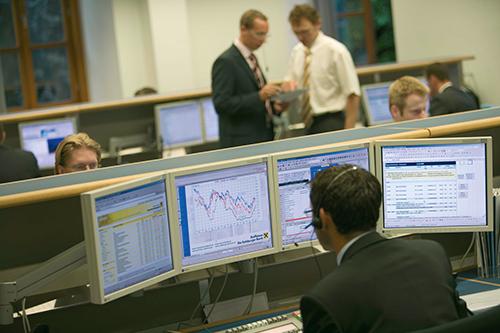 A man reads trades across four computer screens