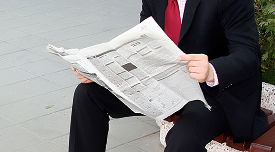 A man in a suit and red tie reads an open newspaper