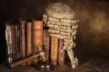 Judges wig resting on old books. Article 50