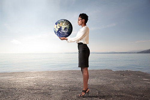 African businesswoman holding the Earth in her hands