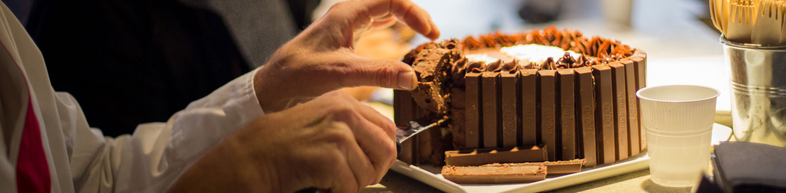 Obscured party guests cut a lice of decadent chocolate cake.