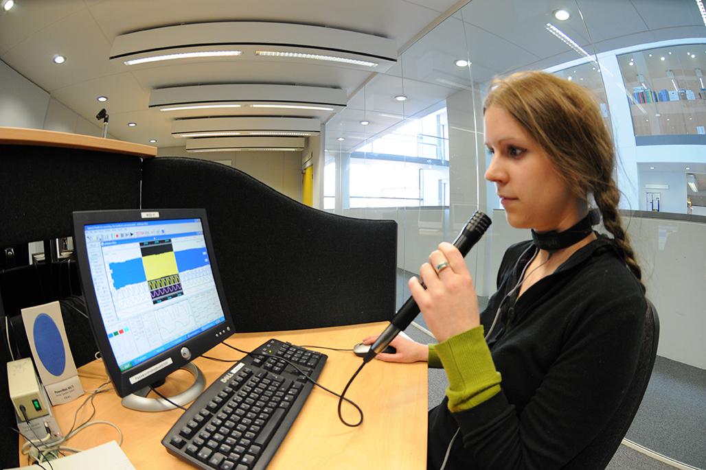 Female student using the phonetics lab equipment