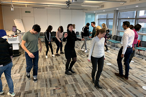 Mindfulness and improv workshop taking place at Cass Business School, with staff and students dancing and moving around the office space.