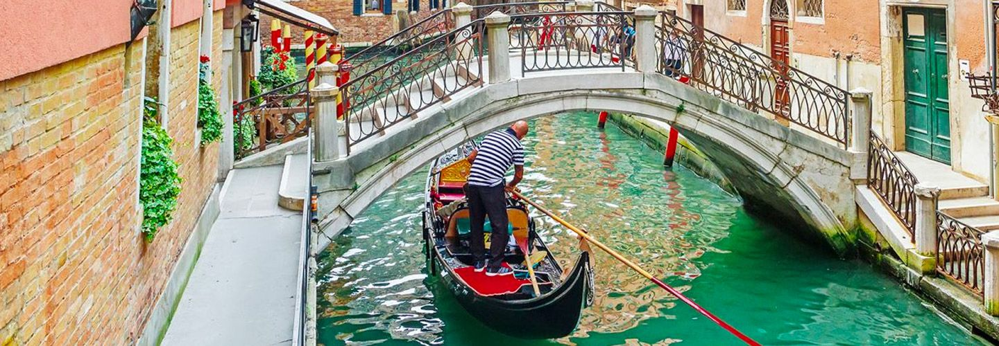 Canal boat passing under a bridge in Venice