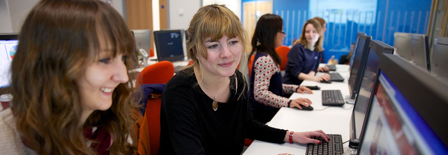 Female postgraduate students smiling in front of a computer screen