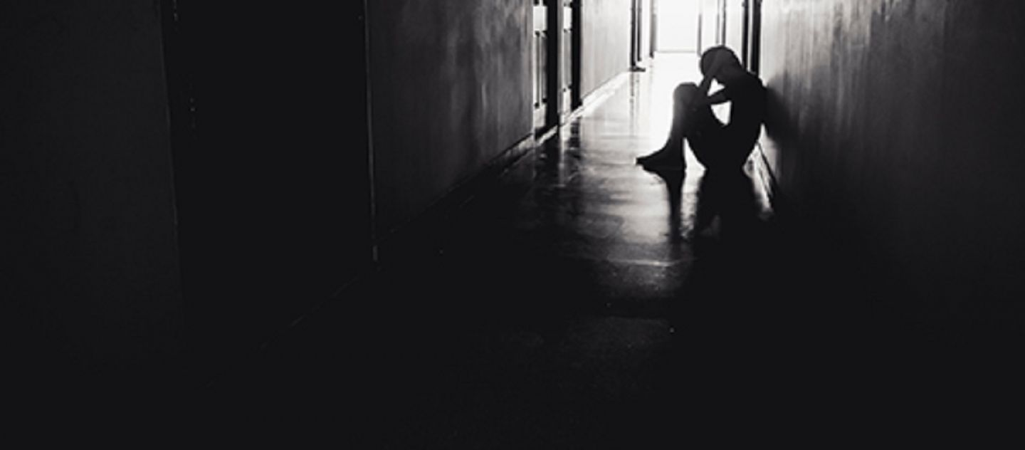 black and white silhouette of a sad person sitting in a corridor with head in hands