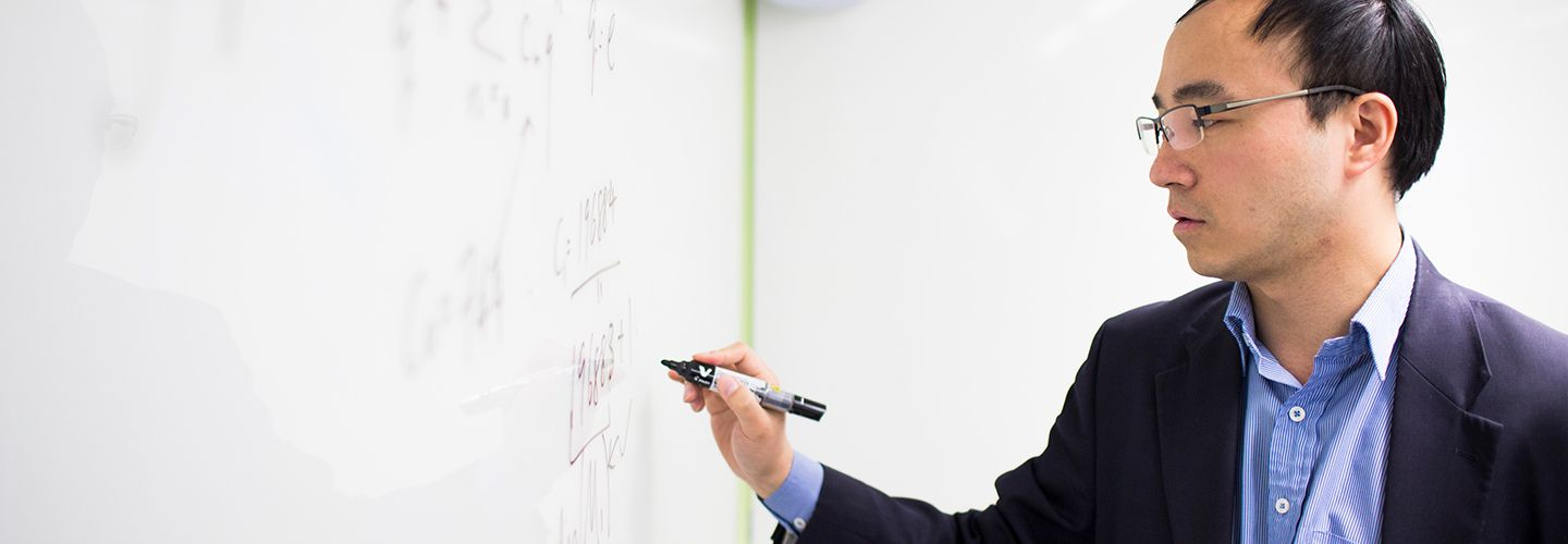 Professor Yang writing an equation on a whiteboard