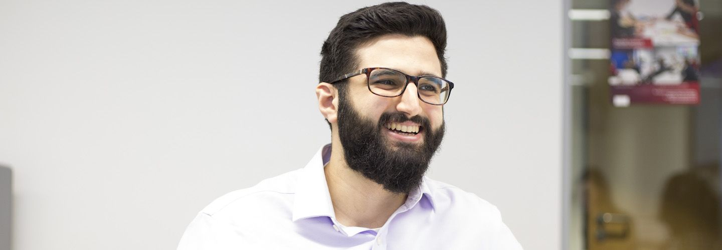 A male student smiling in a lecture