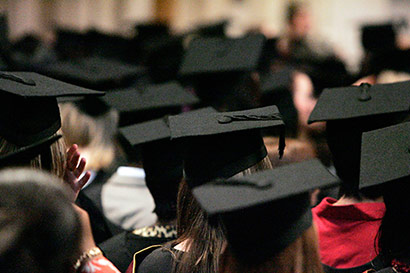 Back view of students in graduation gowns and caps