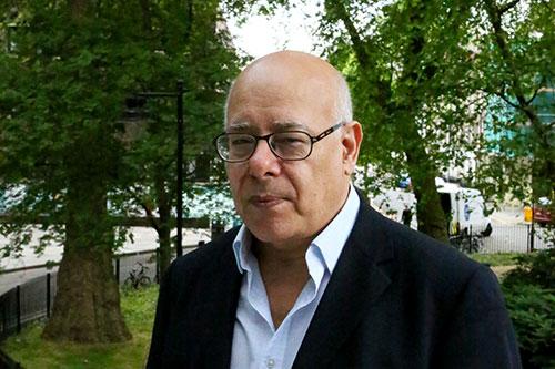 Ahmed El Sharif wearing glasses in front of a garden