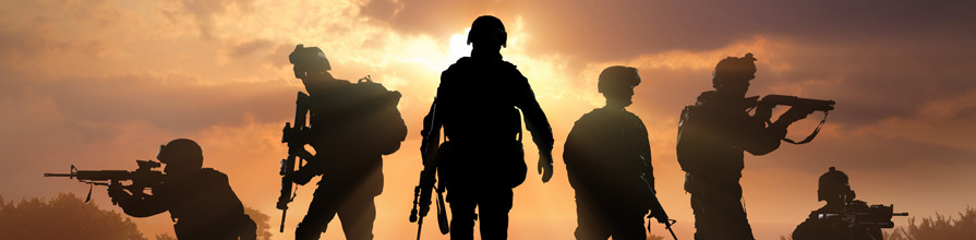 Military men silhouettes on a hill