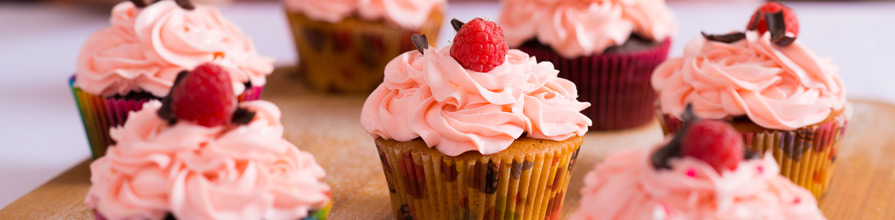 Cupcakes with pink icing and raspberries on top