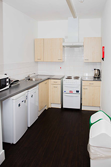 Kitchen in shared flat at Alliance House - two fridges, double oven, microwave, sink and draining board, kettle. Two draw and cupboard units, large under sink cupboard, three wall cupboards