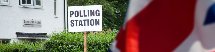 Polling station sign next to union jack. General election