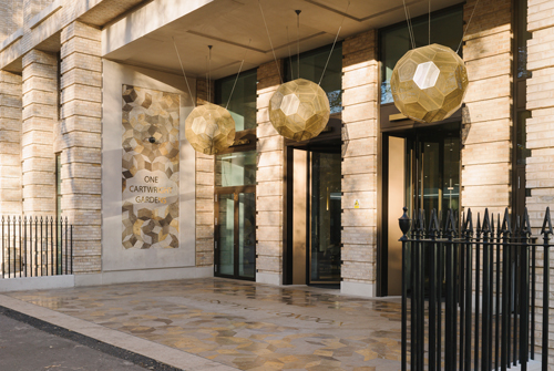 Beige stone entrance with gold honeycomb lights at Cartwright gardens student accommodation.