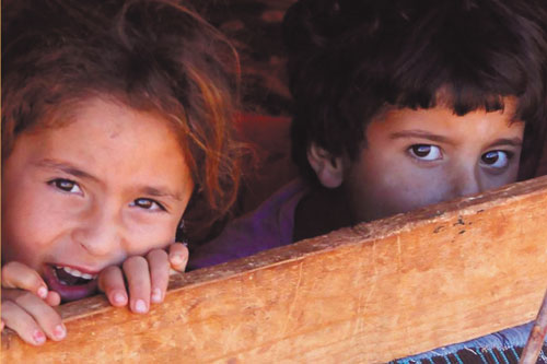 Children peering through a fence; from the cover of Reporting in the Middle East edited by Zahera Harb