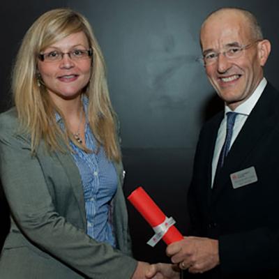 Zoe Cornish receiving an award from Paul Curran