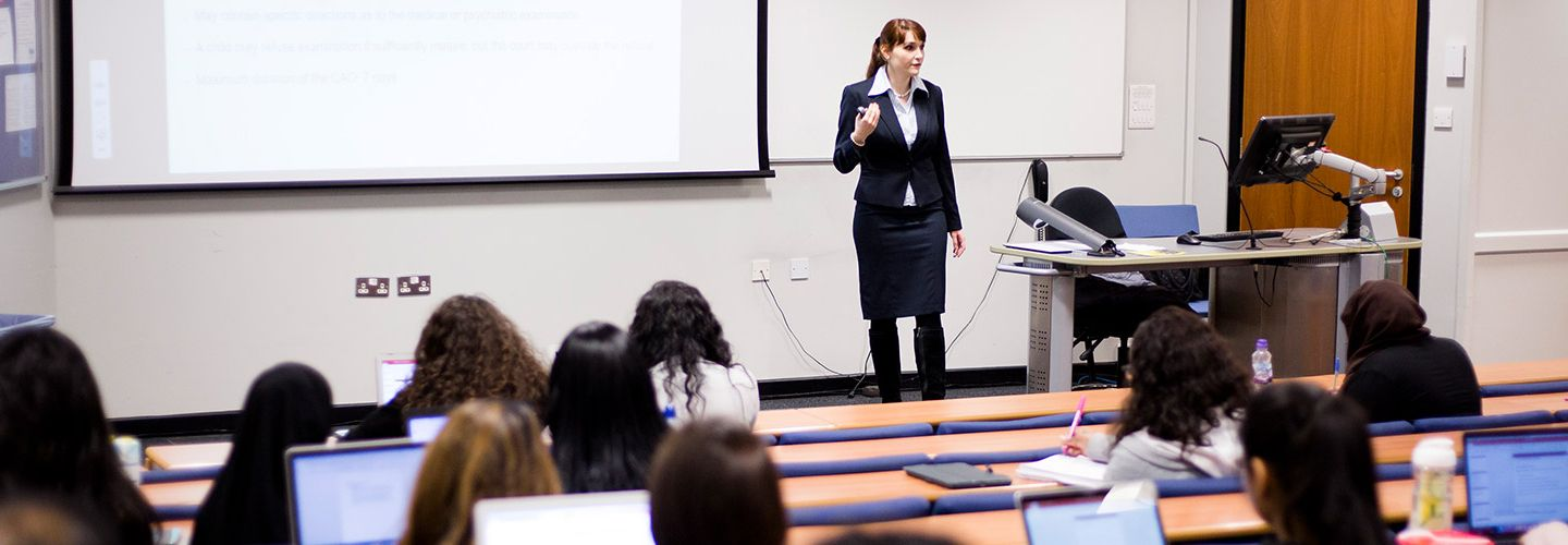 Female academic presenting in a lecture room full of students