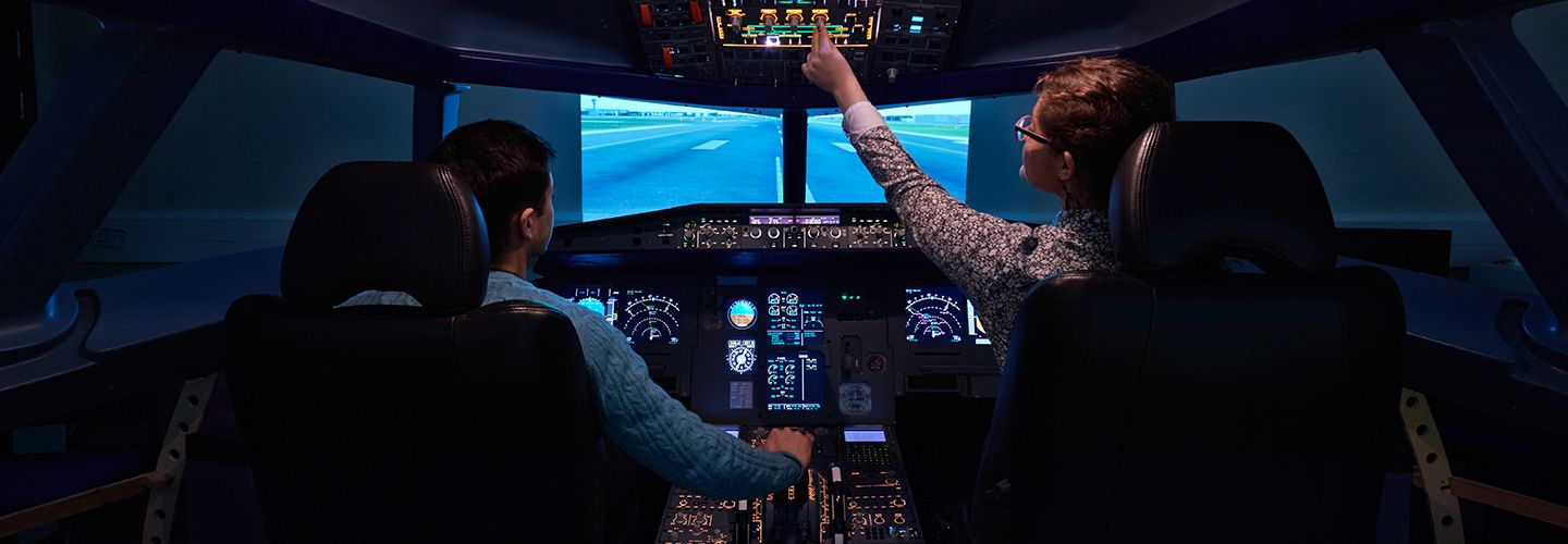 Two students inside a flight simulator
