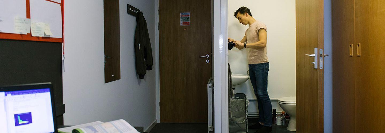 Male student unpacking toiletries in en-suite bedroom
