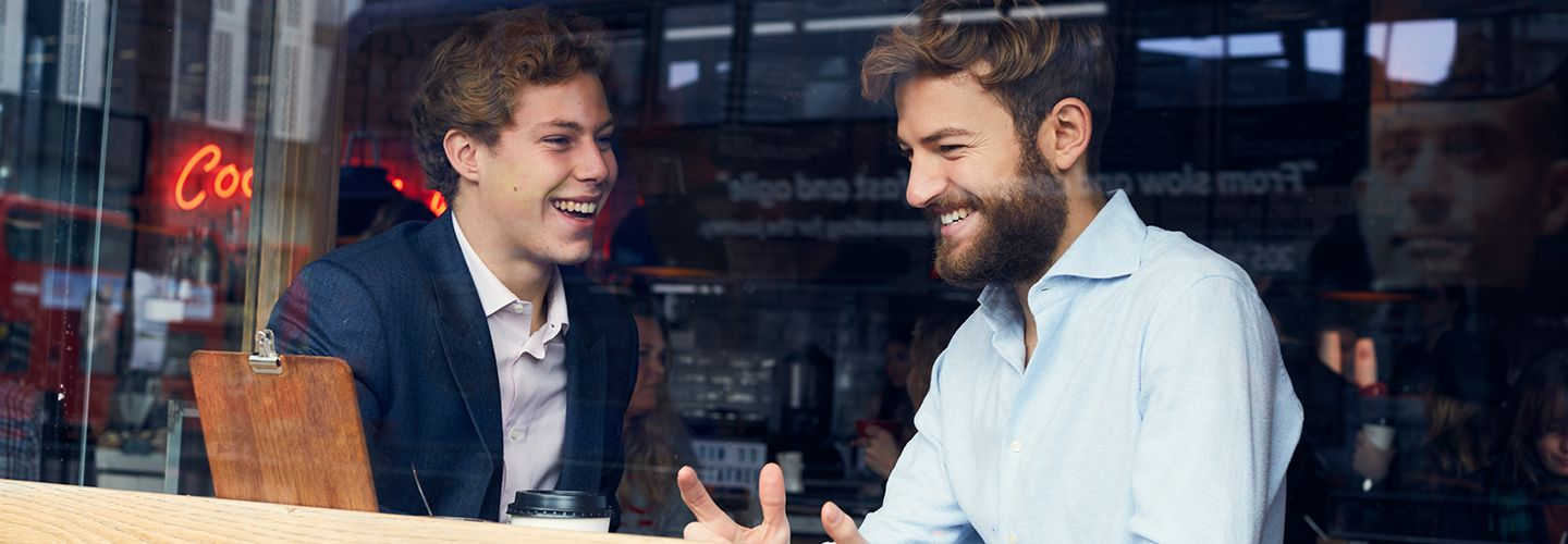 Two male students having a chat inside a coffee shop
