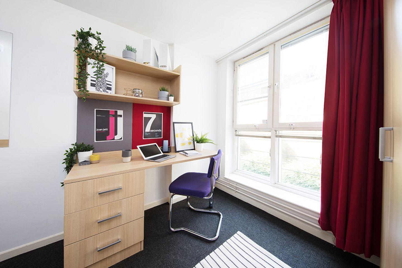 Romano court bedroom featuring desk area