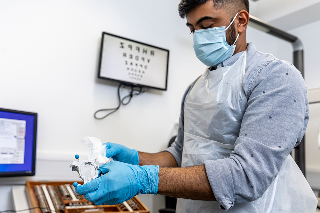 Male student wearing mask and gloves whilst cleaning optometry lens