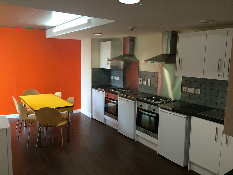 Alliance House shared kitchen featuring yellow table and chairs, from back of kitchen