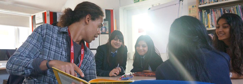Male student volunteer reading to school pupils