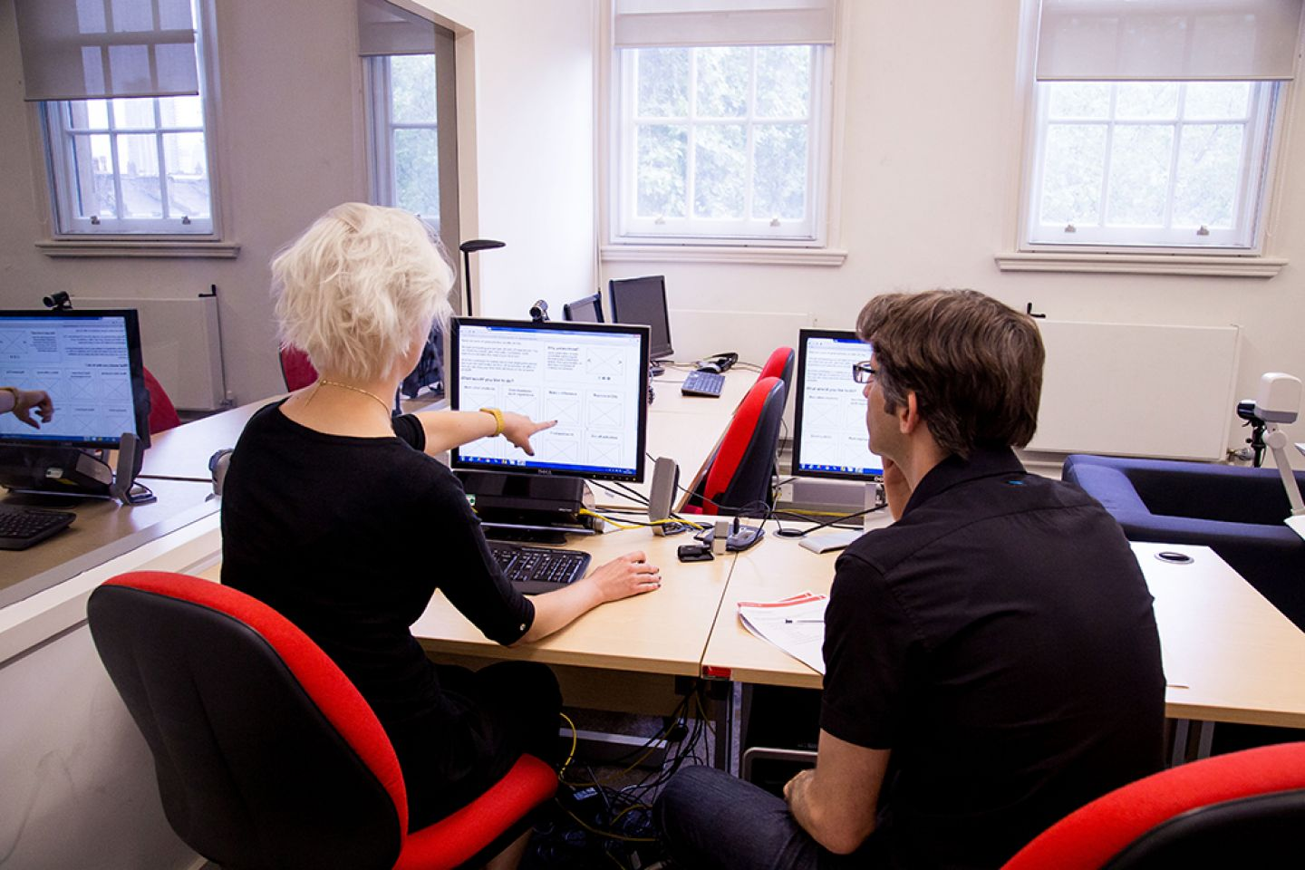 Male conducting user testing with participant on a computer