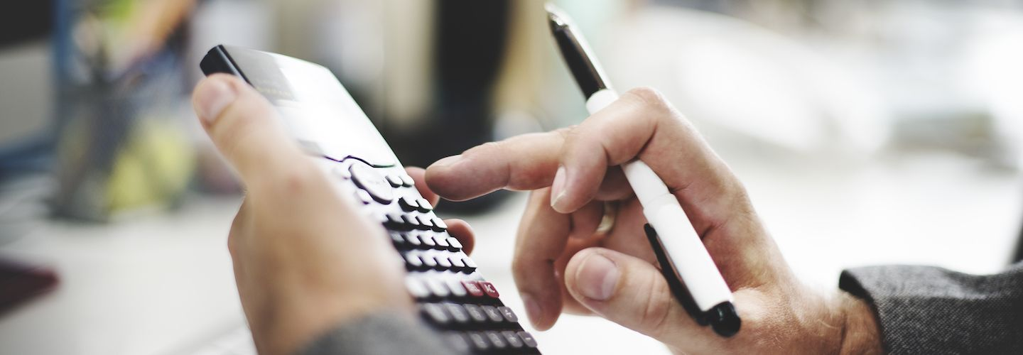 A man's hands holding a pen and using calculator