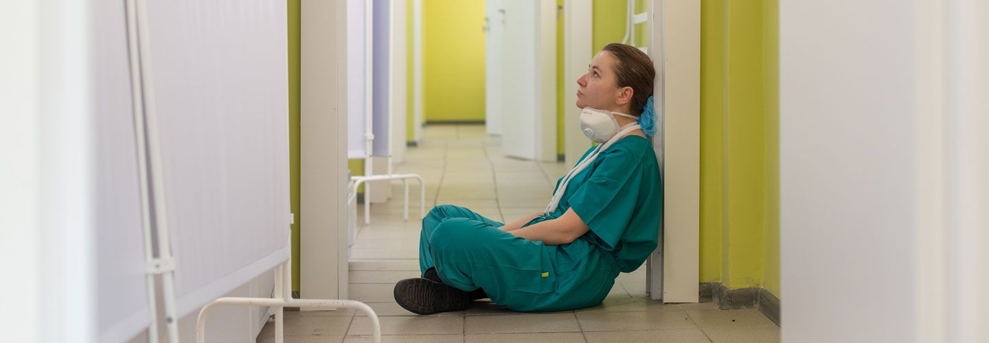Covid nurse sitting on the floor looking tired and thoughtful