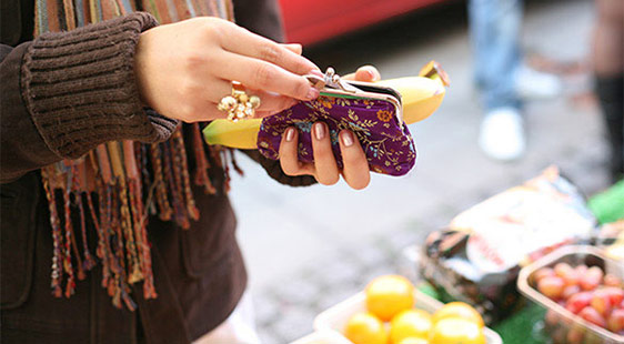 A woman buying a banana from a market stall
