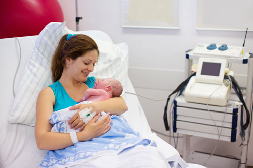 A mother holds her newborn child in a hospital bed
