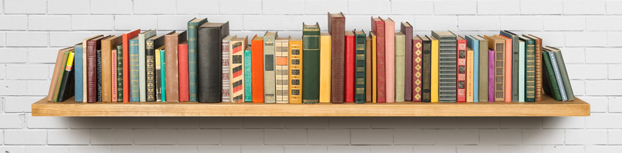 Set of books on shelf on white wall