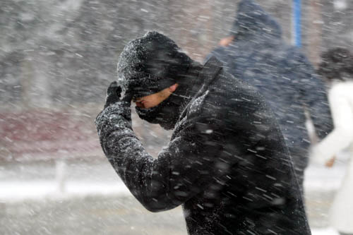 A man walks through a wild snowstorm holding a scarf to his face.