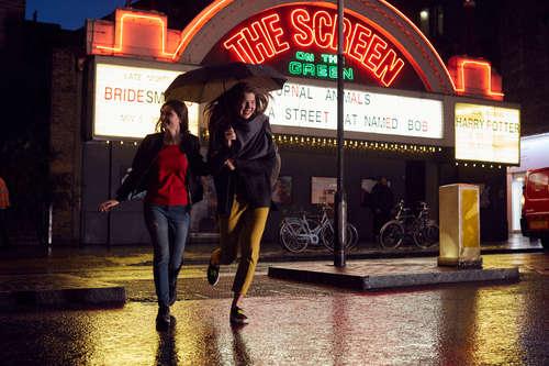 Girls running in the rain laughin