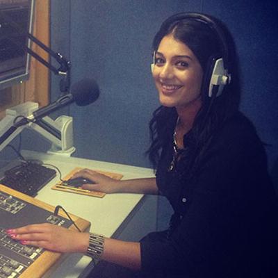 Kiran Kaur smiling in a recording room