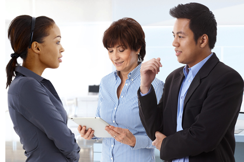 A man and two women stand talking in the office