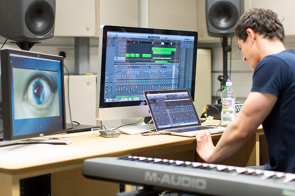 Male music student mixing sounds in a music studio using a laptop.