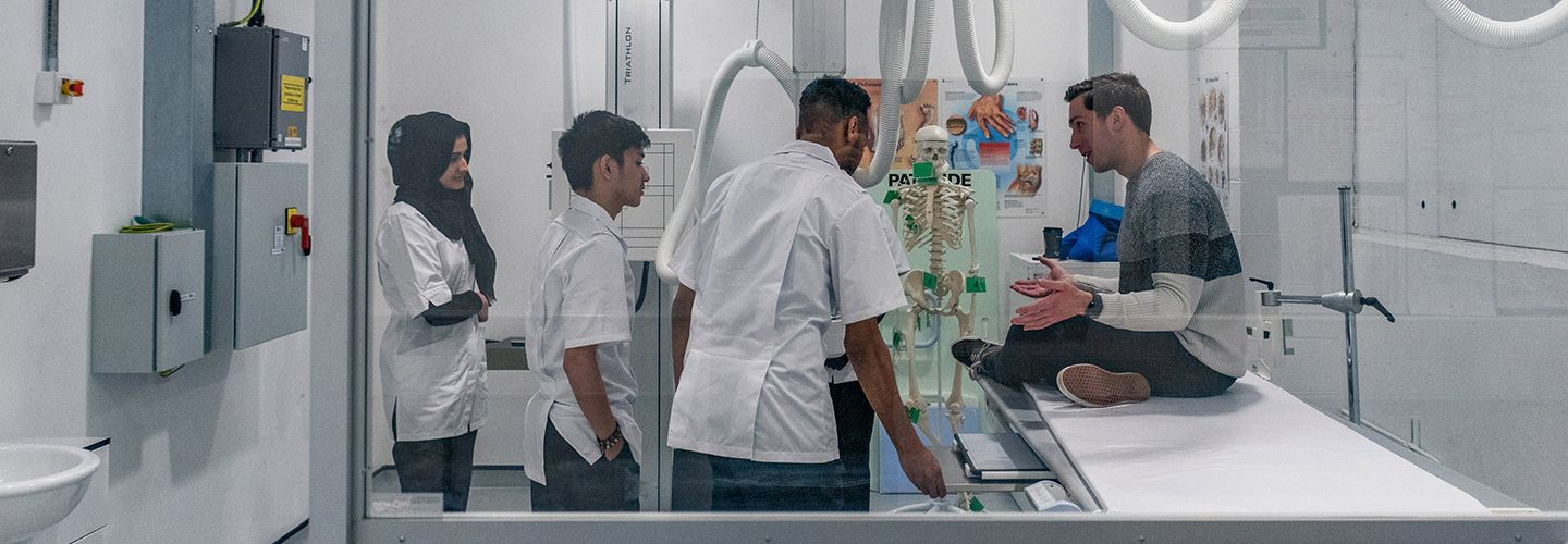 Male academic and students in a practical lesson in radiography lab