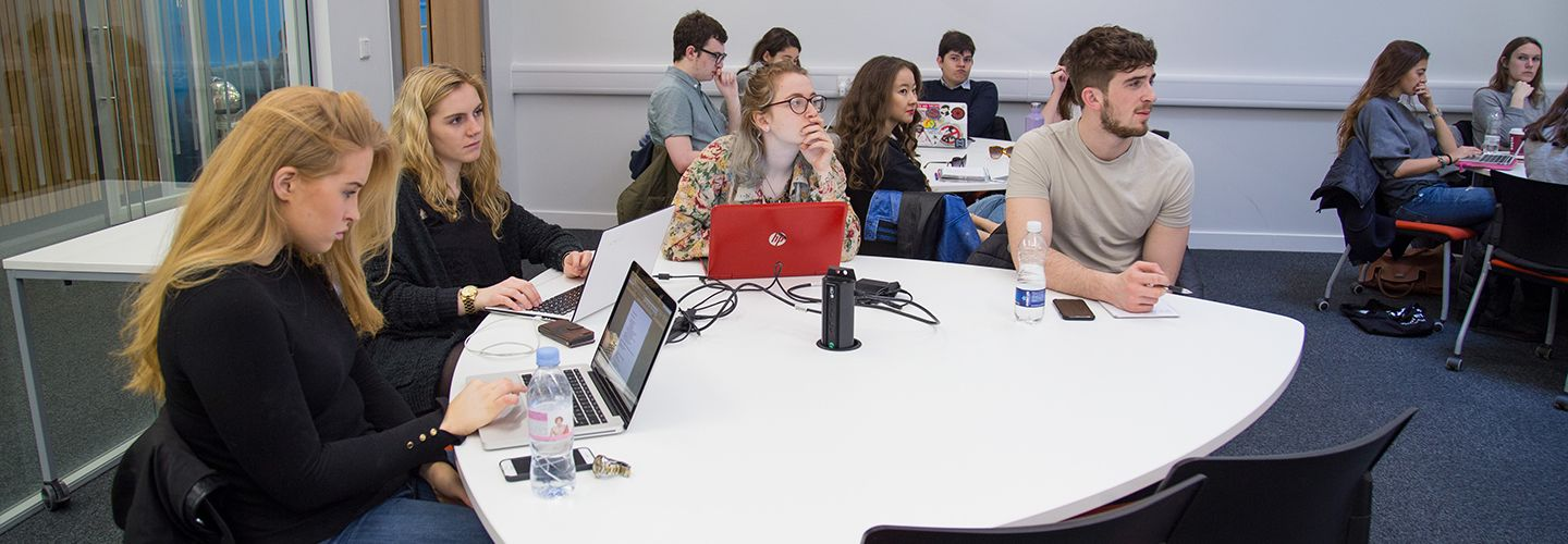 Students sat around the table with laptops listening