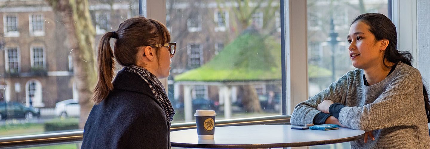 Two female students chatting over coffee with Northampton Square visible from the window.