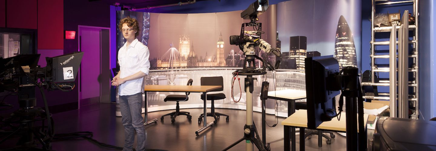 Male student standing in the television studio