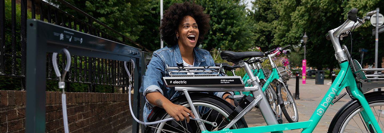 Woman happy unlocking beryl's electric bike-share