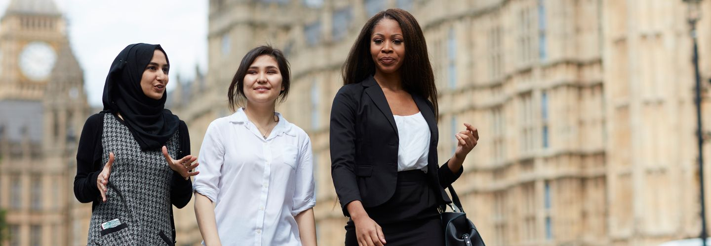 Three diverse young women walking past Westminster and talking.