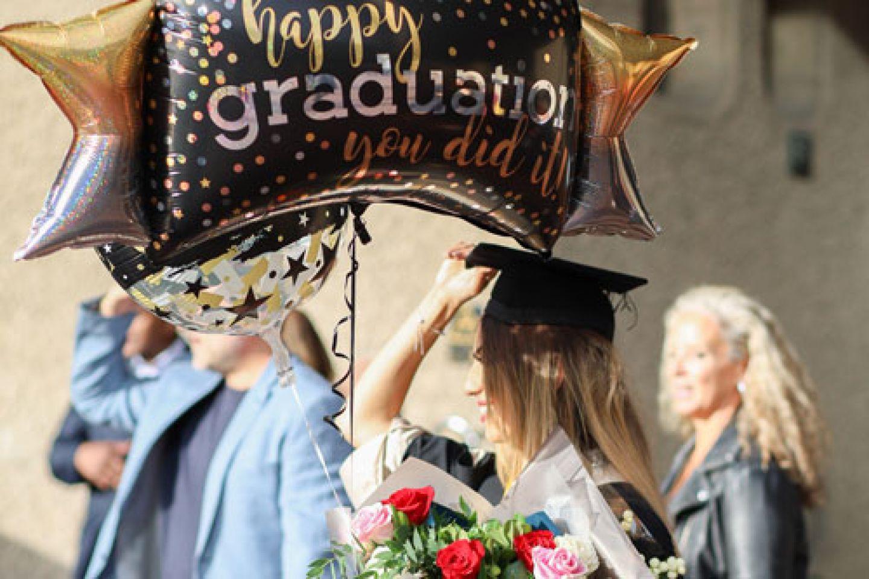 One graduate celebrates with graduation balloons.