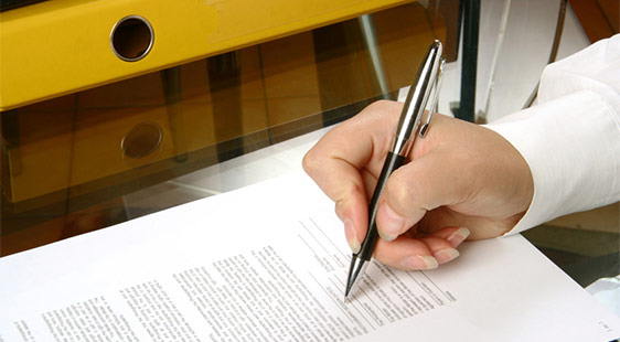 A male hand signing a contract