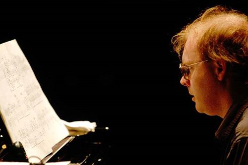 Ian Pace playing the Piano, looking at the music sheets