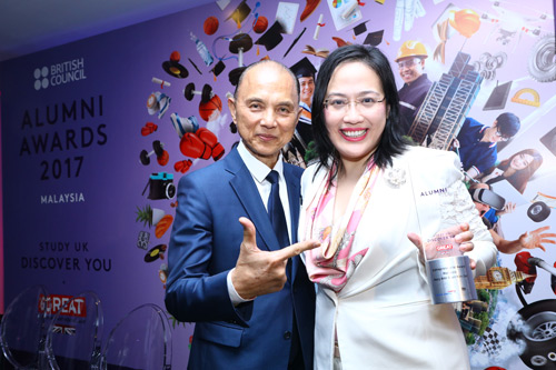 Mary Ann Ooi Suan Kim, City Law School alumna with Jimmy Choo, in front of a poster at the British Council Alumni Awards 2017 in Malaysia.